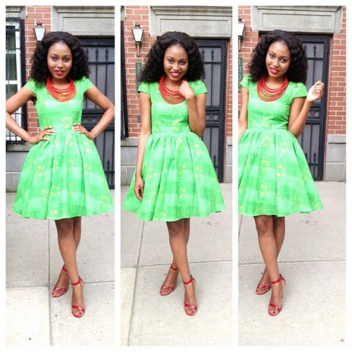 Beautiful lady spotting short flare Ankara gown with cute designs of green and matching red sandals and neck beads. This style is meant to be copied.